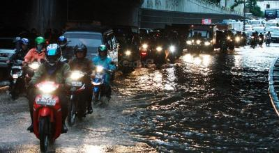 Ini Bahayanya Pemotor Berhenti di Trotoar saat Pakai Jas Hujan